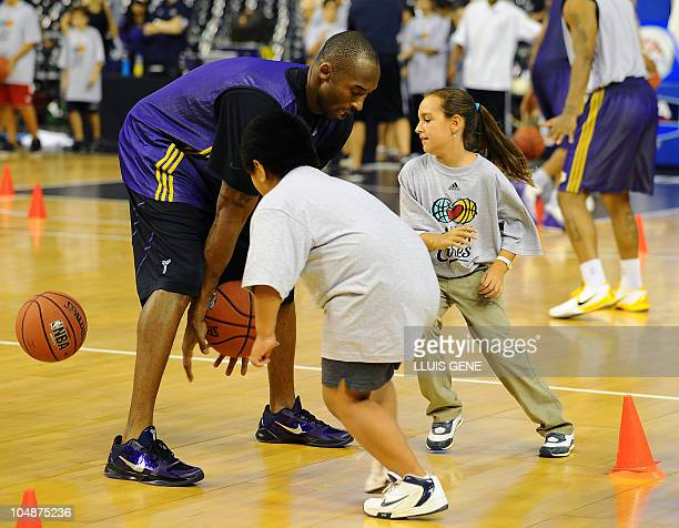 Los Angeles Lakers' Kobe Bryant plays with children during a basketball clinic held after a training session on October 6 2010 at Palau Sant Jordi in...