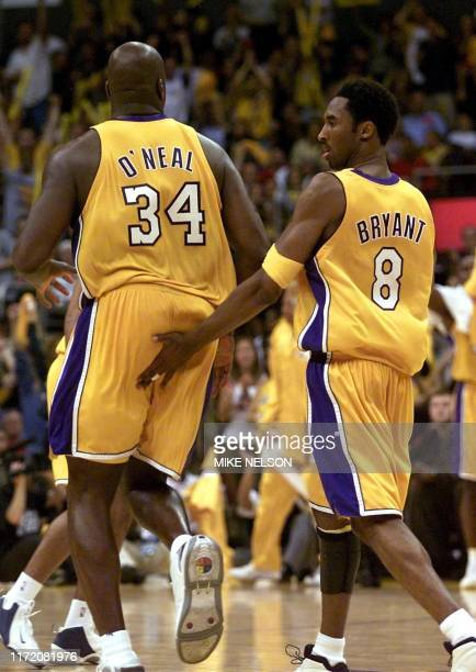 Los Angeles Lakers Kobe Bryant smacks Shaquille O'Neal on the buttocks during game two of the NBA Finals against the Philadelphia 76ers 08 June 2001...