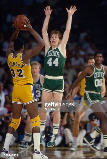 Los Angeles Lakers Magic Johnson looks to pass the ball around the raised-arms of Boston Celtics Danny Ainge during 1985 NBA Finals between Los...