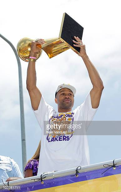 Los Angeles Lakers point guard Derek Fisher hoists the championship trophy while riding in the victory parade for the the NBA basketball champion...