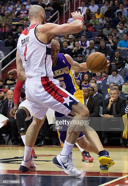 Los Angeles Lakers point guard Steve Blake drives under the basket against Washington Wizards center Marcin Gortat during the first half of their...