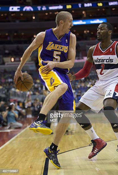 Los Angeles Lakers point guard Steve Blake passes the ball behind his back around Washington Wizards point guard John Wall during the first half of...