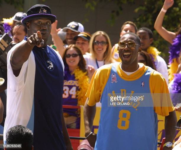 Los Angeles Lakers' Shaquille O'Neal and Kobe Bryant smile as they are honored on a stage at City Hall in Los Angeles California 14 June 2002 for...