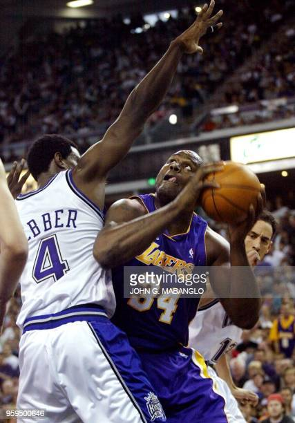Los Angeles Lakers' Shaquille O'Neal goes under Sacramento Kings' Chris Webber during the first period of their NBA game 24 March 2002 in Sacramento...