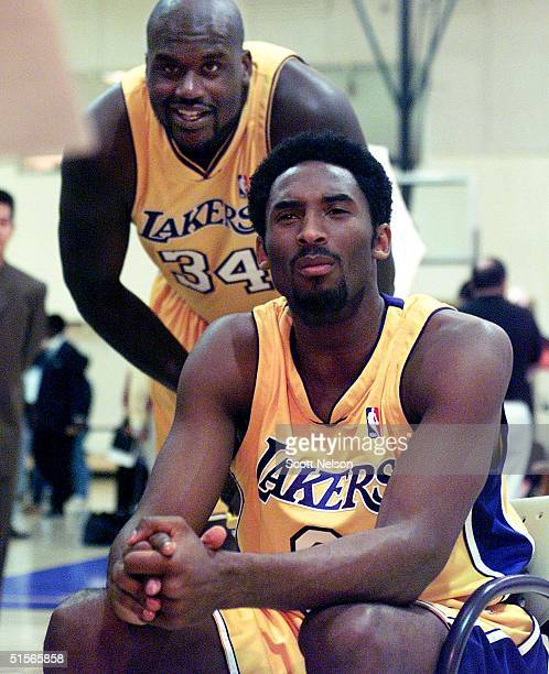 Los Angeles Lakers Shaquille O'Neal looks over the shoulder of teammate Kobe Bryant as he conducts a television interview 02 October 2000 during...