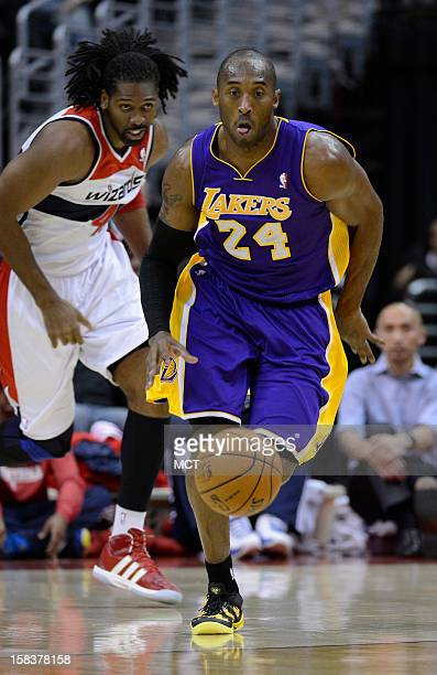 Los Angeles Lakers shooting guard Kobe Bryant breaks up court with the ball ahead of Washington Wizards center Nene during the first half at the...