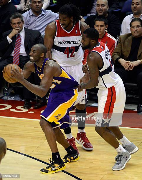 Los Angeles Lakers shooting guard Kobe Bryant escapes a double team by Washington Wizards center Nene and Wizards small forward Martell Webster in...