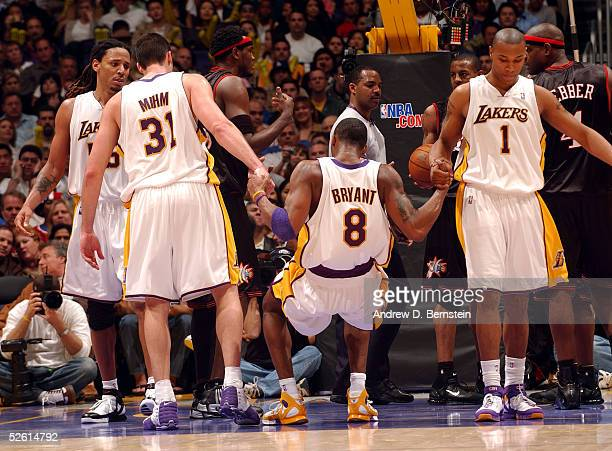 Los Angeles Lakers Slava Medvedenko and Caron Butler help Kobe Bryant to his feet to play against the Philadelphia 76ers on March 27 2005 at the...