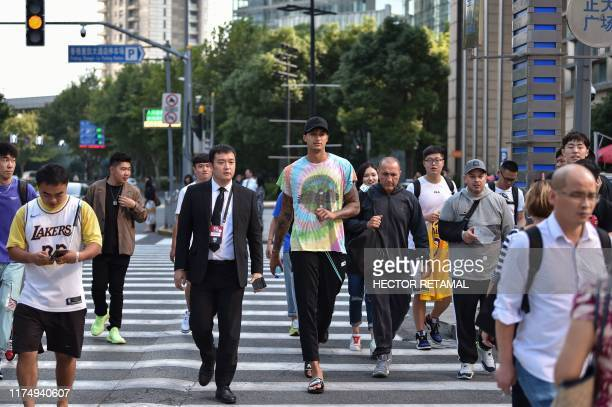 Los Angeles Lakers small forward Kyle Kuzma crosses a street surrounded by fans in Shanghai on October 10 prior to his team's National Basketball...