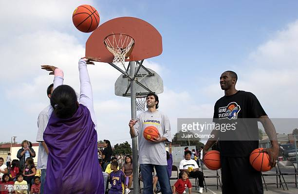 Los Angeles Lakers' Vladimir Radmanovic and Kobe Bryant, help out during a basketball skills clinic as part of a surprise visit by the Lakers to kick...