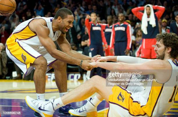 Los Angeles Lakers' Xavier Henry helps up Pau Gasol after Gasol was fouled with the score tied and 6 seconds left on the clock against the Atlanta...