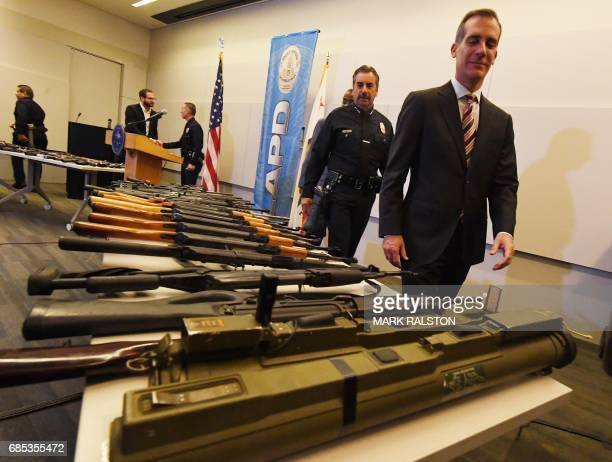 Los Angeles Mayor Eric Garcetti and Police Chief Charlie Beck look at two rocket propelled grenade launchers beside a batch of assault rifles at a...