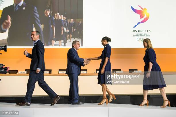 TOPSHOT Los Angeles Mayor Eric Garcetti gives a thumb up as International Olympic Committee President German Thomas Bach greets US Olympic track and...