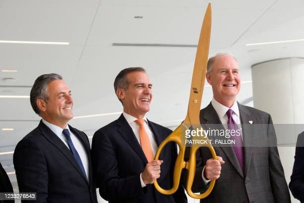 Los Angeles Mayor Eric Garcetti holds an oversized pair of scissors for a ribbon cutting with, Gary Kelly, chief executive officer of Southwest...