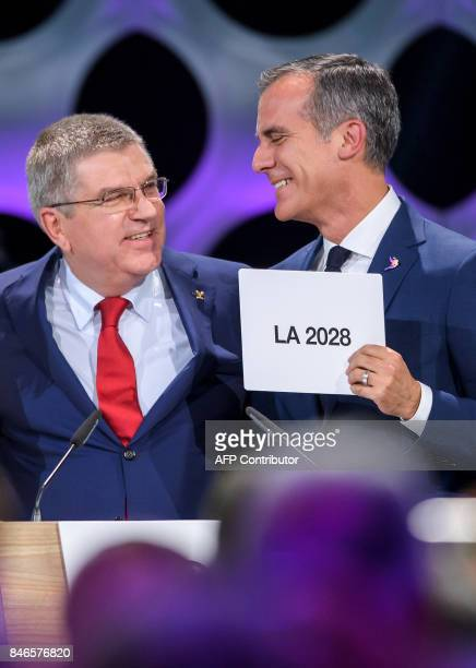 Los Angeles Mayor Eric Garcetti reacts with a card bearing the name of LA 2028 next to International Olympic Committee President Thomas Bach after...