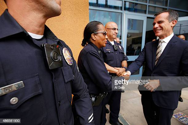 Los Angeles Mayor Eric Garcetti right shakes hands with LAPD officers wearing the new LAPD body camera following a press conference at LAPD Mission...