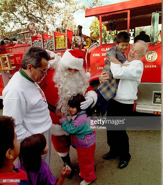 Los Angeles Mayor Richard Riordan rt and Santa Claus are joined by City Councilman Richard Alatorre left and children from Ramona Gardens after...