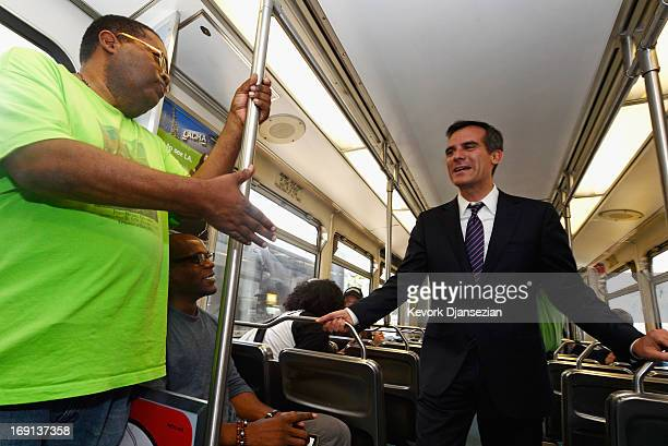 Los Angeles Mayoral candidate and City Councilman Eric Gracetti greets commuters on a Metro train during a campaign stop on May 20 2013 in Los...