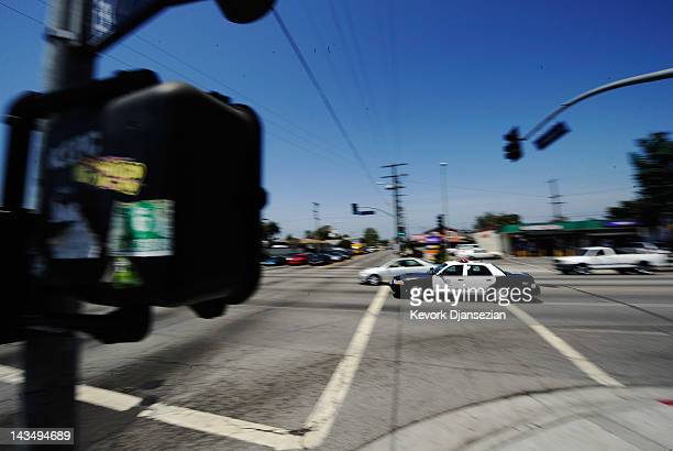 Los Angeles Police Department car with lights and sirens going rushes through the intersection at Florence and Normandy Avenues in South Los Angeles...