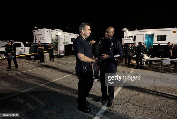 Los Angeles Police Department Chief Charlie Beck and assistant chief Earl Paysinger confer as members of the Los Angeles Police department prepare to...