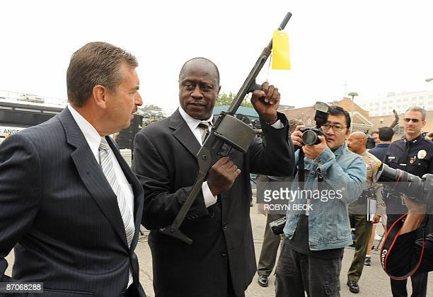 Los Angeles police department Deputy Chief Charles Beck looks on as Lt Fred Booker displays a 12 gauge shotgun assault weapon called a Streetsweeper...