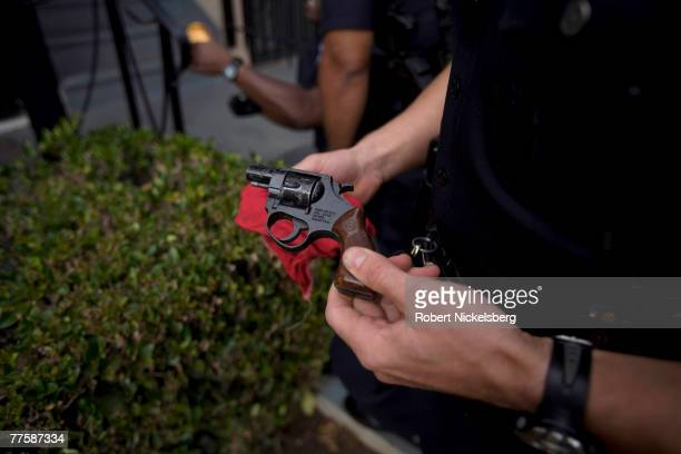 Los Angeles Police Department gang unit officer holds a 22 caliber pistol taken from a suspected drug dealer who ran away from police into an...