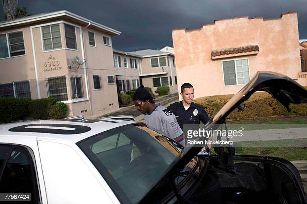 Los Angeles Police Department gang unit officer moves a suspected drug dealer to a police car after he was apprehended with a 22 caliber pistol and a...