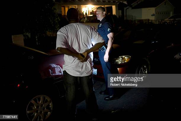 Los Angeles Police Department gang unit officer questions a man seen walking where a gunman was seen fleeing police earlier in the evening September...
