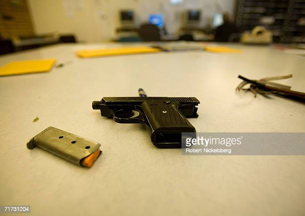 Los Angeles Police Department gang unit officers examine a 9mm pistol used in a hispanic gang shooting outside a bar the previous night on August 5...