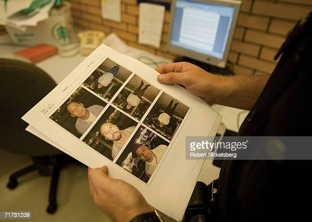 Los Angeles Police Department gang unit officers examine a printout of suspects arrested in a hispanic gang shooting outside a bar the previous night...