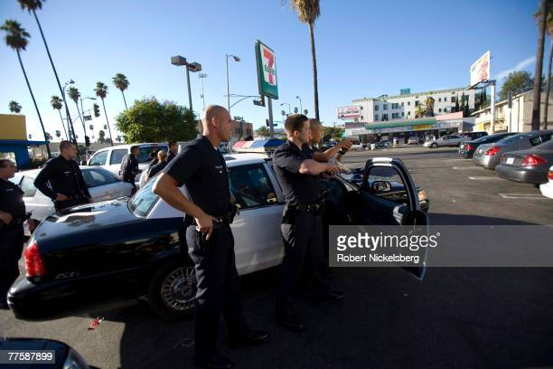 Los Angeles Police Department gang unit officers point their pistols at passengers inside a stolen vehicle September 13 2007 in the Rampart area of...