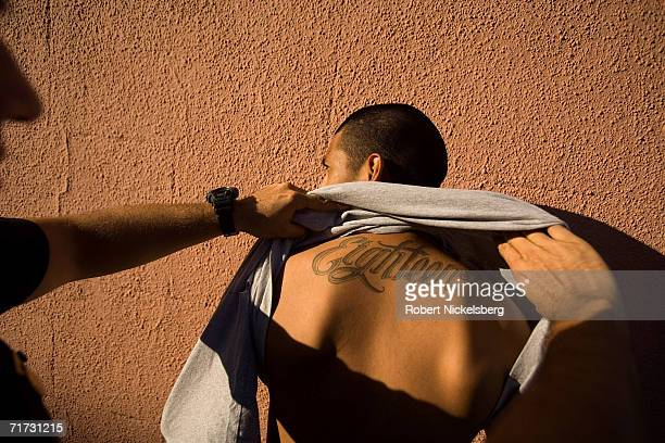 Los Angeles Police Department gang unit officers stop and frisk a known 18th Street gang member on August 5 2006 in the Rampart district of Los...