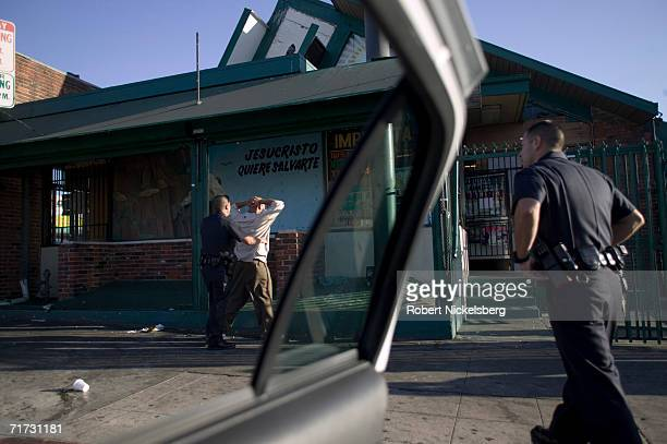 Los Angeles Police Department gang unit officers stop and question a known Crazy Riders gang member on August 5 2006 in the Rampart district of Los...