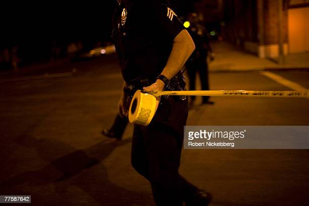 Los Angeles Police Department gang unit officers tape off a Crime Scene Investigation area following the shooting of a man September 14, 2007 in the...