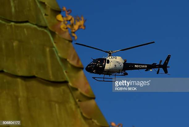 A Los Angeles Police Department helicopter flies over the TCL Chinese Theatre in Hollywood California before the start of the red carpet ceremony for...