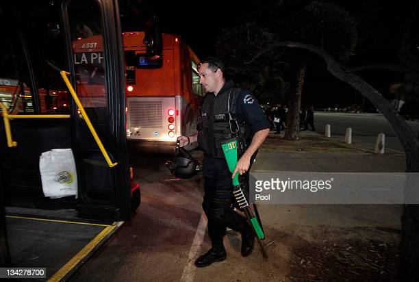 Los Angeles Police Department officer carries his weapon onto a bus transporting police to the Occupy LA encampment outside Los Angeles City Hall to...