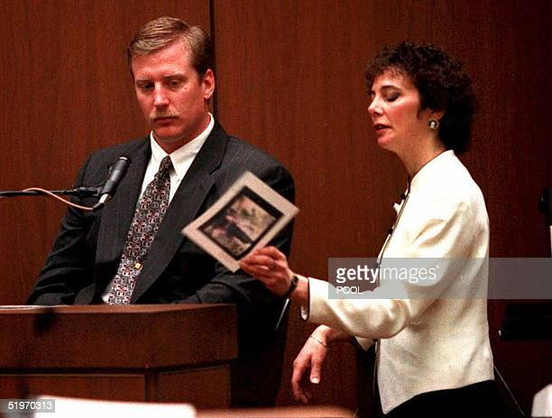 Los Angeles Police Department officer Robert Riske looks at a photograph of the crime scene held by prosecutor Marcia Clark during during the O.J....