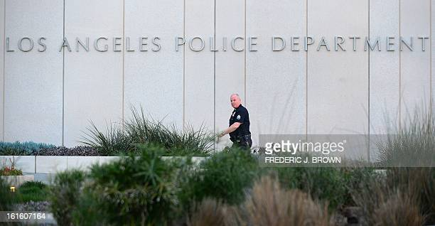 A Los Angeles Police Department officer walks to police headquarters in downtown Los Angeles on February 12 2013 in California where media are...
