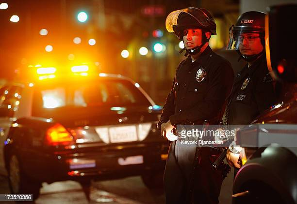Los Angeles Police Department officers in riot gear look at protestors in the streets around Leimert Park following a prayer vigil against the...