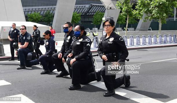 Los Angeles Police Department officers kneel during a rally led by Baptist Ministers to City Hall on June 2 2020 in memory of George Floyd Antiracism...
