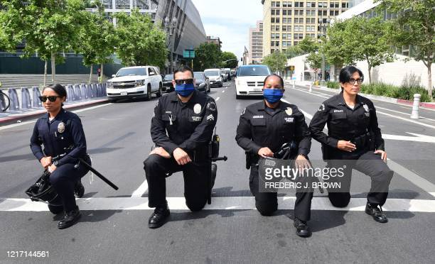 Los Angeles Police Department officers kneel during a rally led by Baptist Ministers to City Hall on June 2, 2020 in memory of George Floyd. -...