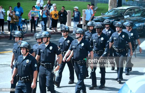 Los Angeles Police Department officers make their way to arrest members of the clergy from different denominations blocking the road in front of the...
