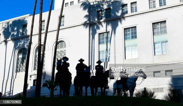 Los Angeles Police Department officers on horseback monitor the situation as social activists gather to mark the inauguration of Joe Biden as the...