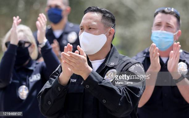 Los Angeles Police Department officers salute healthcare workers after fellow LAPD Detective Michael Chang was released from Providence St. John's...