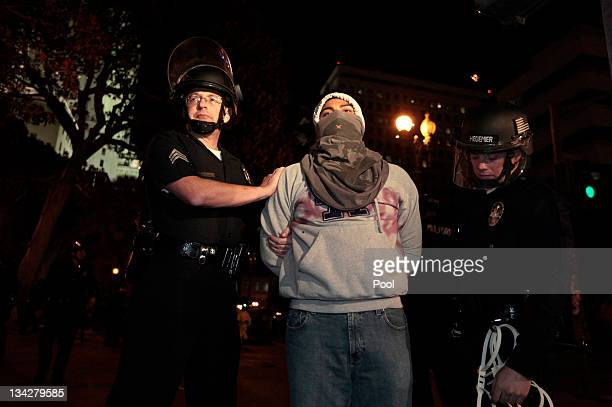 Los Angeles Police Department officers search a protester arrested during the eviction of the Occupy LA tent encampment outside City Hall in the...