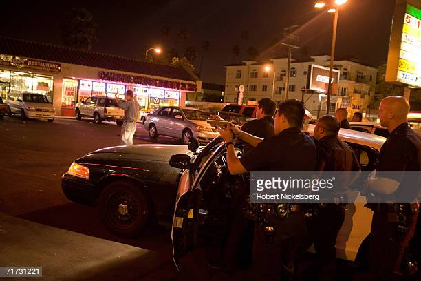 Los Angeles Police Department officers surround a suspect sitting in a van who is possibly involved in a multiple stabbing of three South Asian men...