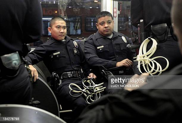 Los Angeles Police department officers wait on a bus as they prepare to evict protesters from the Occupy Los Angeles encampment outside City Hall on...
