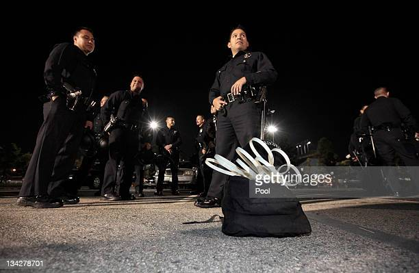 Los Angeles Police department officers wait to board buses to transport them to the Occupy LA encampment outside Los Angeles City Hall to evict...