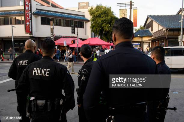 Los Angeles Police Department officers watch as a memorial procession for nursing home residents who died due to Covid-19 proceeds on March 20, 2021...