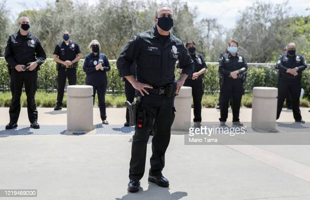 Los Angeles Police Department officers wear face masks as they wait to salute healthcare workers after fellow LAPD Detective Michael Chang was...